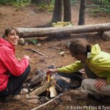 Leah and Benoit starting a campfire from some found wood.