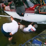 Carl removing float fittings while lying in the lake.