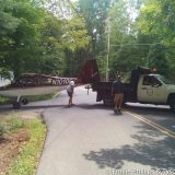 Dump truck slowly towing the fusilage onto Mason Rd.